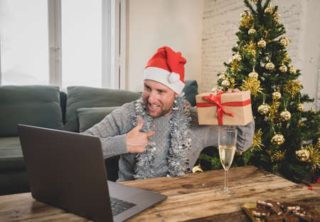 Happy man home alone in lockdown celebrating virtual christmas using laptop video calling family and friends. Virtual holiday gathering online due to coronavirus quarantines and social distancing. Stock Photo