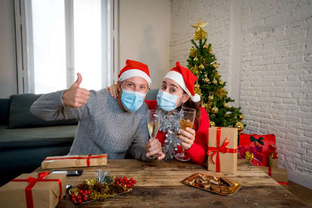 Webcam view of happy couple with face mask on video call celebrating virtual christmas and new year party at home in lockdown. COVID-19 social distancing, self isolation and online celebrations. Stock Photo