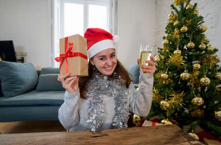 Happy woman celebrating Virtual christmas and new year home alone in lockdown. Webcam view portrait of woman on video call or virtual christmas party. Online celebrations and COVID-19 Outbreak.