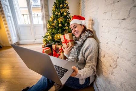 Happy woman alone in lockdown celebrating virtual christmas video calling family and friend. Virtual holiday gathering online due to coronavirus quarantine, social distancing and new restrictions.