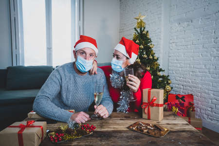Sad couple with mask in self isolation on video call with family missing celebrating christmas and new year face to face. Virtual celebrations and COVID-19 New Normal lockdown and social distancing.