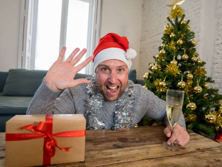 Happy man on video call celebrating christmas and new year online home alone in lockdown. Webcam view portrait. Virtual celebration and COVID-19 New Normal, lockdown, quarantine and social distancing. Stock Photo