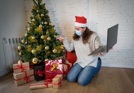 Happy woman with face mask home alone in lockdown celebrating christmas online video calling family and friends. Virtual holiday gathering and celebrations due to coronavirus second outbreak. Stock Photo
