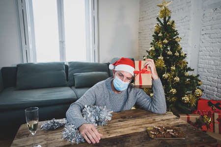 Sad man with mask home alone in self isolation at christmas feeling depressed mourning and missing family and friends. COVID-19 Lockdown and quarantine during winter holidays and mental health. 写真素材