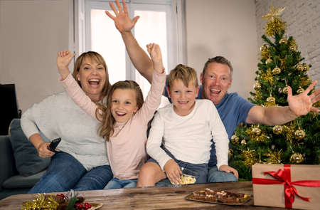 Happy family on video call call celebrating virtual christmas online due to social distancing and coronavirus lockdown and quarantines. Screen device view image of happy virtual celebrations.