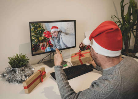 Man on virtual call with girlfriend exchanging gifts and celebrating christmas online due to social distancing and coronavirus lockdown and quarantines. New Normal and virtual christmas celebration.