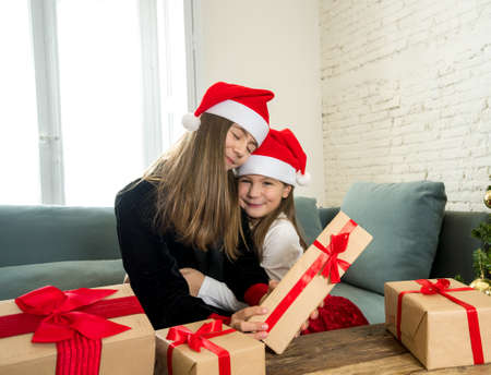 Happy and excited children celebrating holidays showing christmas gifts and wearing santa hats. Webcam view portrait of two girls on video call with family. Virtual christmas in the New Normal. 写真素材