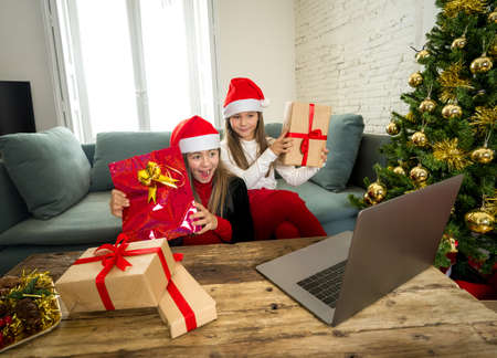 Two Beautiful happy children with computer video calling family and showing christmas presents online. Virtual Holidays celebration due to COVID-19 quarantine, stay home order and social distancing. 写真素材