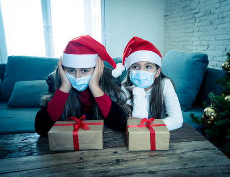 Sad and depressed children with mask at home bored at christmas feeling depressed missing family and friends. COVID-19 Lockdown, quarantine, stay home order, virtual christmas and mental health.