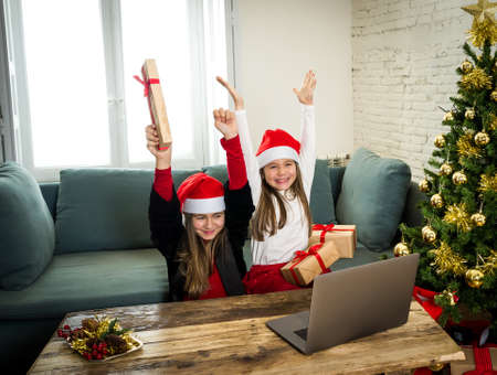 Two Beautiful happy children with computer video calling family and showing christmas presents online. Virtual Holidays celebration due to COVID-19 quarantine, stay home order and social distancing. Zdjęcie Seryjne