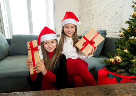 Happy and excited children celebrating holidays showing christmas gifts and wearing santa hats. Webcam view portrait of two girls on video call with family. Virtual christmas in the New Normal. Zdjęcie Seryjne