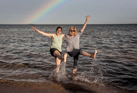 Senior Mother and adult daughter on remote beach enjoying outdoors life spending time together after easing the coronavirus lockdown. Happy family, healthy active people and Hope concept