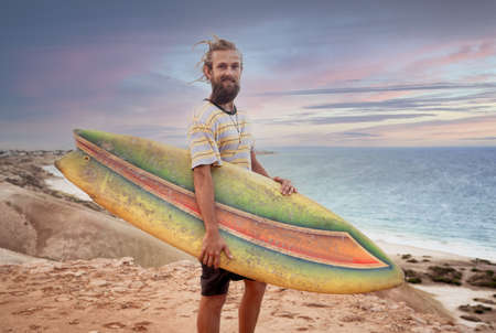 Attractive Blonde Australian hipster surfer with dreadlocks and beard looking at the sea holding cool vintage surfboard at sunset. Back to surf, Outdoors sports adventure lifestyle in the New Normal. Zdjęcie Seryjne