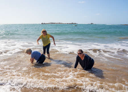 Group of senior retired women on their 60s and 70s falling in the water having fun on the beach. Older ladies laughing as they fall down loosing balance. Humor senior health and aging together. Zdjęcie Seryjne