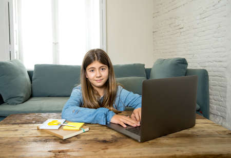 Happy Teen girl on laptop studying online in virtual remote class on the internet at home as high school remain closed due to latest coronavirus lockdown. COVID-19, education, children, E- learning.