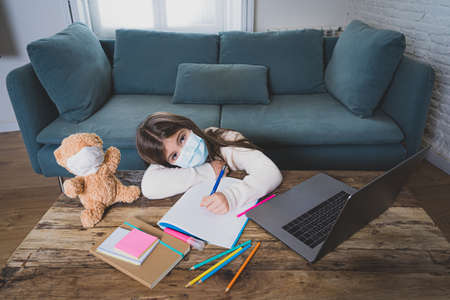 E-learning. Bored and depressed girl with teddy bear and face mask on laptop studying at home in online classes as school remain closed due to New COVID-19 lockdown or forecast weather conditions.