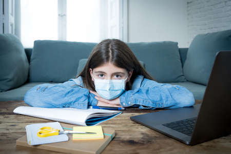 Bored and depressed teenager girl with face mask on laptop studying at home in online education class as high school remain closed due to New COVID-19 lockdown or forecast weather conditions. Zdjęcie Seryjne