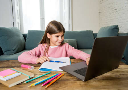Happy Schoolgirl on laptop studying online in a virtual remote class on the internet at home as schools remain closed due to latest coronavirus lockdown. COVID-19, education, children and E- learning.