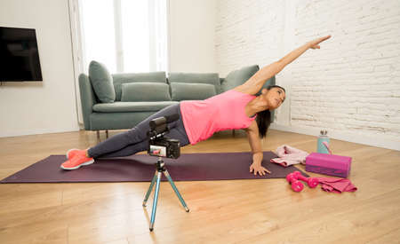 Attractive Woman personal trainer coach recording on camera new content for online fitness business. Freelance filming online training program with virtual workout and exercises for social media.