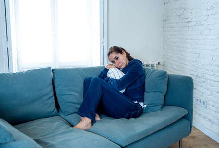 Young lonely attractive latin woman crying on couch feeling sad tired and worried suffering depression isolated at home. Mental Health and lockdown, stress, unemployment and heartbroken concept.
