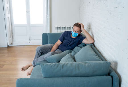 Sad man with protective face mask at home living room couch feeling tired and worried suffering depression amid  lockdown and social distancing. Mental Health and isolation concept.