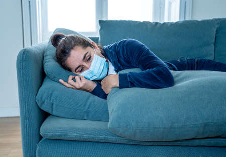 Sad latin woman with protective face mask at home living room couch feeling tired and worried suffering depression amid lockdown and social distancing. Mental Health and isolation concept.