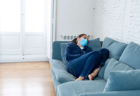 Sad latin woman with protective face mask at home living room couch feeling tired and worried suffering depression amid  lockdown and social distancing. Mental  and isolation concept. 스톡 콘텐츠