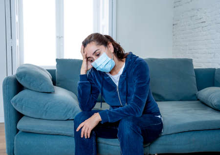 Sad latin woman with protective face mask at home living room couch feeling tired and worried suffering depression amid  lockdown and social distancing. Mental Health and isolation concept. 스톡 콘텐츠