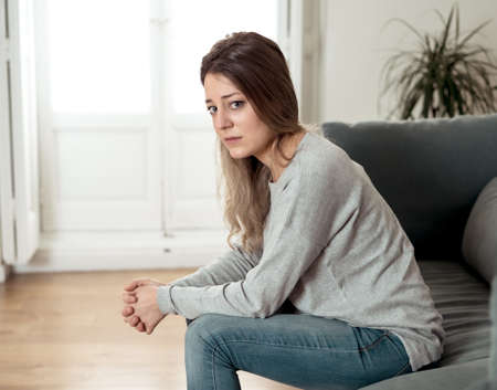 Depressed sad attractive woman crying on sofa couch at home feeling lonely tired and worried suffering depression in mental health, loneliness and isolation concept. Psychology, solitude and people