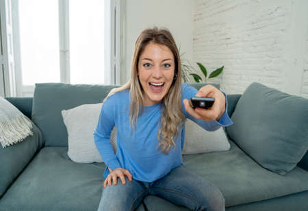 Happy woman on sofa with TV remote control ready to watch favorite movie of TV Show. Looking enthusiastic, making gestures of approval. In people, stay home and leisure concept.