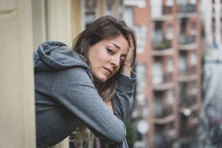 Young caucasian sad and depressed woman standing on a balcony feeling stressed and overwhelmed. Female suffering from depression in Mental Health concept