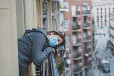 Beautiful depressed lonely woman staring out feeling sad, pain, grief on a balcony at home. Crisis, depression and mental health concept. Reklamní fotografie