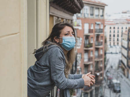 Beautiful depressed lonely woman with face mask in quarantine staring out on balcony feeling sad, lonely, pain and grief during outbreak. Depression and mental health
