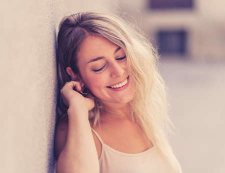 Outdoors close up portrait of young attractive woman with beautiful blonde hair and sensual smile. Female model posing with natural beauty and light. Real People, beauty care, fashion and lifestyle. Foto de archivo