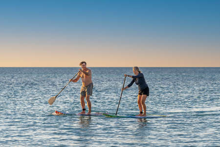 Mature caucasian couple on SUP paddleboarding having fun on quiet calm sea at sunset in beautiful remote beach. Active modern older people, outdoors activities, aging together and healthy lifestyle.