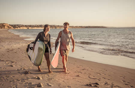 Mature couple with surfboards on beautiful beach enjoying paradise and active lifestyle. Attractive fit man and woman surfing and having fun. In travel, active healthy people and outdoors sports.
