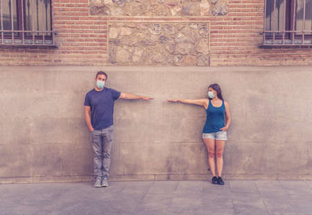 Man and woman wearing protective face masks standing 2 m from each other keeping social distancing the spread Foto de archivo