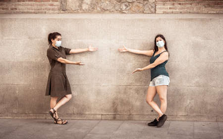 Two woman wearing protective face masks standing 2 m from each other keeping social distancing avoiding the spread
