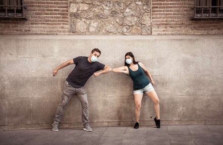 Man and woman wearing protective face masks standing 2 m from each other keeping social distancing the sprea Foto de archivo
