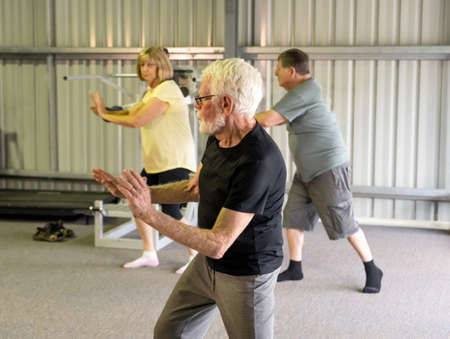 Group of seniors in Tai Chi class exercising in an active retirement lifestyle. Mental and physical health benefits of exercise and fitness in elderly people. Senior health care and wellbeing concept.