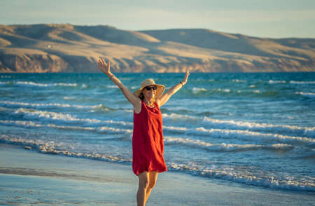 Happy attractive Mature woman in red dress enjoying outdoors and freedom on the beach, open arms outstretched with blue ocean and beautiful landscape. Retirement lifestyle and Wellbeing concept. Foto de archivo