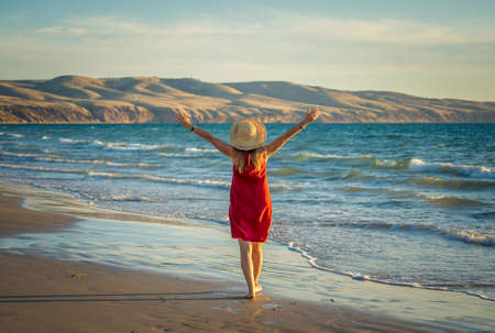 Happy attractive Mature woman in red dress enjoying outdoors and freedom on the beach, open arms outstretched with blue ocean and beautiful landscape. Travel, People, Hope and Wellbeing concept. Foto de archivo