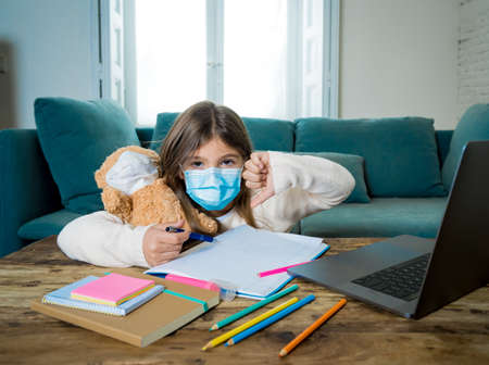 E-learning. Bored and depressed girl with teddy bear and face mask on laptop studying at home in online classes as school remain closed due to New lockdown or forecast weather conditions.