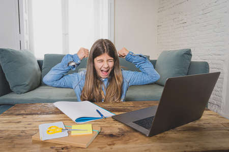 Happy Teen girl on laptop studying online in virtual remote class on the internet at home as high school remain closed due to latest virus lockdown.