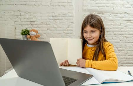 Happy Schoolgirl on laptop studying online in a virtual remote class on the internet at home as schools remain closed due to latest virus lockdown.