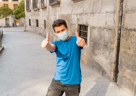Happy young man with surgical face mask outdoors showing thumbs up. Man with protective mask walking in city street after virus outbreak lockdown. Positive image New Normal life Standard-Bild