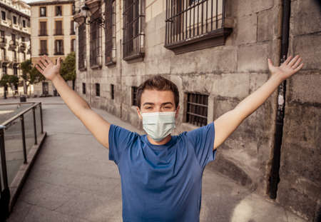 Young man wearing surgical face mask in public spaces. Man with protective mask happy to walk outdoors city street after virus outbreak lockdown. Positive image of New Normal life