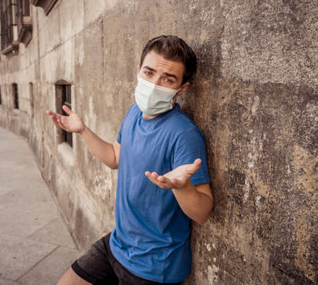 Young sad desperate man wearing surgical face mask in public spaces. Man with protective mask walking outdoors city street after virus outbreak lockdown. New Normal life Standard-Bild