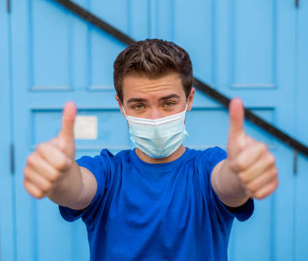 Young man wearing medical protective surgical face mask against infectious virus disease. Conceptual portrait of New Normal