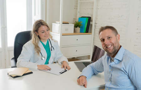 Smiling female doctor and happy patient man talking in hospital clinic office. Medical exam, Health care, professional medical staff, happy hospital environment, Insurance and Medical trust concept. Banco de Imagens
